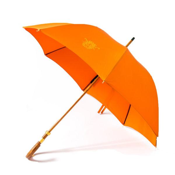 Le parapluie de cherbourg Le Milady en orange , accastillage or fin 24 carats, poignée courbe en jonc, ouvert